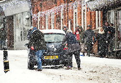 © Licensed to London News Pictures. 10/12/2017. Tring, UK. People attempt to push cars, stuck in the snow, through the town of Tring in  Buckinghamshire, England as parts of the south east of England are blanketed with snow for the first time this winter. Photo credit: Ben Cawthra/LNP