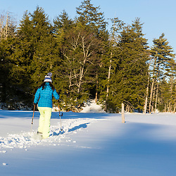 A teenage girl snowshoes across a frozen beaver pond in Epping, New Hampshire.