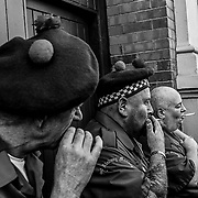 Loyalist Protestants break for cigarettes after the parade outside of their headquarters. Northern Ireland, September 2019
