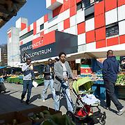 Nederlands Amsterdam Bijlmermeer 29 maart 2011 20110329 Wijkmarkt Kraaiennest, publiek winkelt,  verkoop van oa groente en fruit  op de markt. Op de achtergrond het karakteristieke winkelcentrum Kraaiennest. Foto: David Rozing