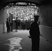 A matador walks out of the main part of the stadium after a fight through a dark tunnel