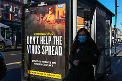 © Licensed to London News Pictures. 25/01/2021. London, UK. A woman wearing a protective face covering walks past the government's 'Don't Help The Virus Spread' publicity campaign poster in north London. Prime Minister Boris Johnson is set to approve plans for Australia-style hotel quarantines for anybody returning from abroad, who will have to spend ten days isolating in a hotel at their own expense. Photo credit: Dinendra Haria/LNP