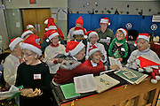 Holiday singing with piano and Christmas hats at community art and cookie celebration.