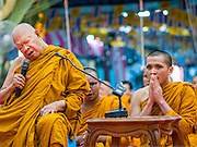 11 JANUARY 2015 - BANGKOK, THAILAND: The abbot at Wat Dhamma Mongkol leads prayers during a three day retreat to practice the Eight Precepts at Wat Dhamma Mongkol in Bangkok. Buddhist precepts are moral guidelines Buddhists follow rather than commandments in the Christian sense of the word. As Buddhists develop in the Dhamma, they find that the Precepts grounds their practice. One cannot waver and purposely break any of the Precepts. The Eight Precepts are typically also practiced during intensive meditation retreats of one day or longer. Wat Dhamma Mongkol, (pronounced 'Dhammamongkon') is on the edge of Bangkok, and visible from a number of places, especially from the elevated expressways around the city. The temple was started in the early 1960s by a revered monk who had spent more than 20 years in a forest retreat. The 95 meter high tower, completed in 1985, is a modern rendition of the tower that now marks the place of the Buddha's enlightenment in Bodhgaya, India. There are classrooms, a museum and meditation area inside the tower. The largest Buddha statue carved from a single piece of jade is on the temple grounds.   PHOTO BY JACK KURTZ