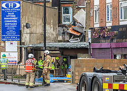 CAPTION CORRECTED FOR DATE ERROR © Licensed to London News Pictures. 20/10/2020. London, UK. Fire crews and emergency services at the scene of a suspected gas explosion where a partially collapsed building can be seen in Kings Street, Southall. A suspected gas explosion has ripped though a building in Kings Street, Southall in West London. Seven fire engines and over 30 crews were called to an explosion in West London where a building had collapsed and rescued several people from the property. Photo credit: Alex Lentati/LNP