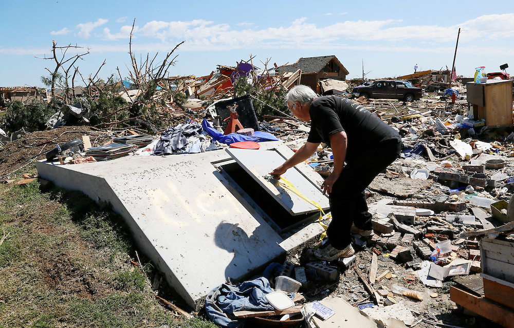 Charles Taber opens the two-week old storm shelter that saved his life in the May 20, 2013 tornado in Oklahoma City, Oklahoma May 22, 2013. Nine people rode out the storm in the shelter as their neighborhood above was decimated.  Rescue workers with sniffer dogs picked through the ruins on Wednesday to ensure no survivors remained buried after a deadly tornado left thousands homeless and trying to salvage what was left of their belongings.  REUTERS/Rick Wilking (UNITED STATES)