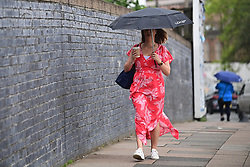 © Licensed to London News Pictures. 17/06/2021. London, UK. A member of the public shelters from the rain underneath an umbrella in Queens Park, London, as wet conditions move in to southern England, replacing weeks of warm dry weather. . . Photo credit: Ben Cawthra/LNP