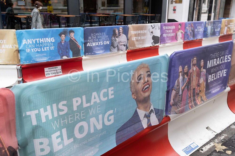 A pedestrian walks down St. Martin's Lane in the heart of the capital's West End Theatreland, where street barriers featuring some of the many musical and stage plays are featured on social distance street barriers during the Coronavirus pandemic,  on 29th September 2020, in London, Westminster, England. Despite the government's £1.15bn financial rescue package for the Arts industry and cultural organisations in England , made up of £880m in grants and £270m of repayable loans, London's theatre industry has been hit hard by the pandemic, being closed since the March lockdown closures which has affected 137,250 Arts industry jobs, worth £21.2bn in direct turnover.