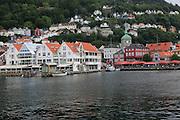 View over water to historic buildings in Vagen harbour area to Torget fish market, city of Bergen, Norway