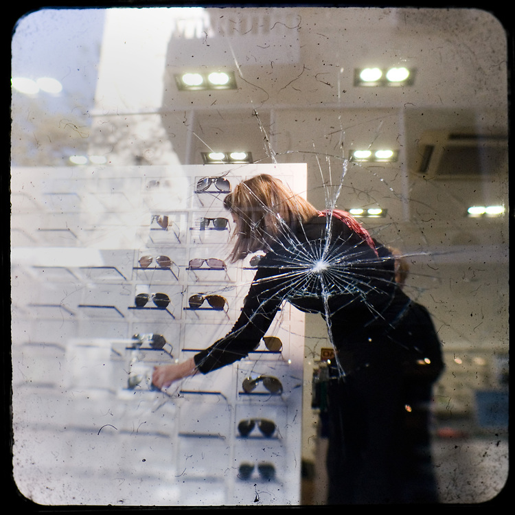 A woman clears up after rioters damaged a shop selling glases on Akadimias street. <br /> <br /> Following the murder of a 15 year old boy, Alexandros Grigoropoulos, by a policeman on 6 December 2008 widespread riots, protests and unrest followed lasting for several weeks and spreading beyond the capital and even overseas<br /> <br /> When I walked in the streets of my town the day after the riots I instantly forgot the image I had about Athens, that of a bustling, peaceful, energetic metropolis and in my mind came the old photographs from WWII, the civil war and the students uprising against the dictatorship. <br /> <br /> Thus I decided not to turn my digital camera straight to the destroyed buildings but to photograph through an old camera that worked as a filter, a barrier between me and the city.