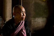 A female Cambodian monk rests inside a temple ruin at the Angkor complex in Siem Reap, Cambodia.
