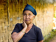 Wearing her traditional headscarf made from indigo dyed cotton, La, a Laopan ethnic minority woman stands outside her bamboo home in Ban Laopan, Phongsaly province, Lao PDR. One of the most ethnically diverse countries in Southeast Asia, Laos has 49 officially recognised ethnic groups although there are many more self-identified and sub groups. These groups are distinguished by their own customs, beliefs and rituals. Details down to the embroidery on a shirt, the colour of the trim and the type of skirt all help signify the wearer's ethnic and clan affiliations.