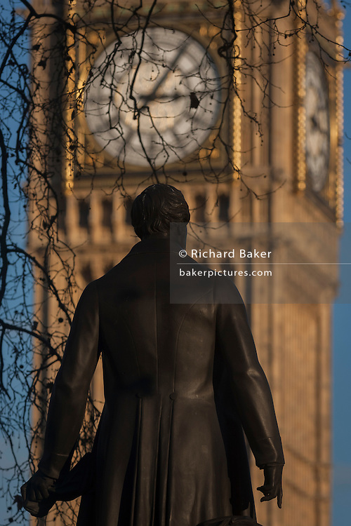 """The statue of Sir Robert Peel and the Elizabeth Tower of the British Houses of Parliament, on 17th January 2017, in Parliament Square, London England. The Elizabeth Tower (previously called the Clock Tower) named in tribute to Queen Elizabeth II in her Diamond Jubilee year – was raised as a part of Charles Barry's design for a new palace, after the old Palace of Westminster was largely destroyed by fire on the night of 16 October 1834. The new Parliament was built in a Neo-gothic style, completed in 1858 and is one of the most prominent symbols of both London and England. Sir Robert Peel, was a British statesman and member of the Conservative Party, served twice as Prime Minister of the United Kingdom and twice as Home Secretary. He created the modern police force and officers known as """"bobbies"""" and """"peelers"""""""