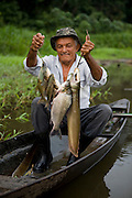 João Agustinho Cardoso, fishes in a shallow lake near the Solimoes River in Manacapuru, Brazil. (Featured in the book What I Eat: Around the World in 80 Diets.) The caloric value of his day's worth of food for a typical day in the month of November was 5200 kcals. He is 69 years of age; 5 feet 2.5 inches tall and 140 pounds.  João's new house has no electricity and the toilet is simply the end of the big balsa wood logs the house is floating on. There is, however, running water, and plenty of it, in the half-mile-wide branch of the river they live on. Unfortunately the water is not potable, but it is teeming with fish, including piranha, which can make swimming during the early morning or evening worrisome. The curimata in the photo is just one of dozens of species that makes its way onto João's table. Absent from his daily diet are any alcoholic or caffeinated beverages, eschewed by his Seventh-day Adventist religion.  MODEL RELEASED.