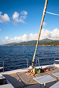 A middle aged woman enjoying a book on the deck of a charter boat while cruising up the coast of Guadeloupe in the French Caribbean