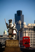 As a bus drives over London Bridge, a griffin statue marks the southern boundary between Southwark on the south side and the City of London beyond on the bridge. The City of London is a geographically-small City within Greater London, England. The City of London is the historic core of London from which, along with Westminster, the modern conurbation grew. The City's boundaries have remained constant since the Middle Ages but  it is now only a tiny part of Greater London. The City of London is a major financial centre, often referred to as just the City or as the Square Mile, as it is approximately one square mile (2.6 km) in area. London Bridge's history stretches back to the first crossing over Roman Londinium, close to this site and subsequent wooden and stone bridges have helped modern London become a financial success.