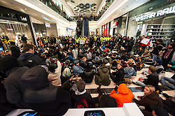 © Licensed to London News Pictures. 10/12/14. London UK. Hundreds of protesters stage a 'die-in' inside Westfield Shopping Centre in West London, over the grand jury decision not to indict a police officer involved in the death of Eric Garner. The die-in was organised by London Black Revs, who launched the action in solidarity with a wave of protests in the US over the death of Eric Garner by a white New York City police officer. There were over 50 arrests including 3 legal observers. After being kettled, protesters were arrested en mass and processed by Met Police Evidence Gatherers and taken away on two TfL double decker buses to police stations around London. Photo credit : Guilhem Baker/LNP
