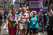 """New York, NY - 25 June 2017. New York City Heritage of Pride March filled Fifth Avenue for hours with groups from the LGBT community and it's supporters. A young woman with a T-shirt reading """"I [heart] my moms"""" marching with both her moms, one of whom carries a sign reading """"resist the war against women."""""""
