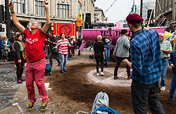 A man dances to a DJ on the boat as hundreds of environmental protesters from Extinction Rebellion occupy Oxford Circus, a pink yacht being the focal point of their presence, with traffic denied access to two of London's busiest streets. London, April 16 2019.