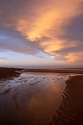 A winter sunset red sky over the long sandy beach of Sutton on Sea, Lincolnshire. United Kingdom. Sutton on Sea is on the coast of the North Sea, and is a popular holiday destination up the coast from Skegness.