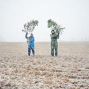 Yhteiskuva kaadetun puun oksien kanssa.