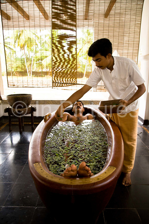 A patient lies near fully submerged in a wooden tub of herb infused water for promote relaxation during the process of detoxification as part of the Ayurvedic treatment process.  Ayurveda is considered a holistic Indian medicine dating back to ancient times, Kollengode, Kerala, India