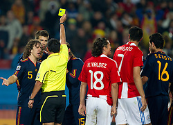 Carles Puyol of Spain, Gerard Pique of Spain and referee Carlos Batres with yellow card for Pique and penalty shot for Paraguay during the  2010 FIFA World Cup South Africa Quarter Finals football match between Paraguay and Spain on July 03, 2010 at Ellis Park Stadium in Johannesburg. Spain defeated Paraguay 1-0. (Photo by Vid Ponikvar / Sportida)