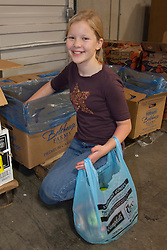 North America, United States, Washington, Kirkland, female teenager working in food bank warehouse.  MR