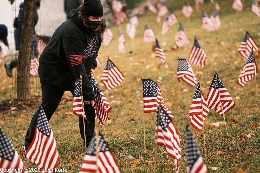10 SEPTEMBER 2020 - DES MOINES, IOWA: TRACY STAMPER, from Des Moines, places American flags on the shore of Gray's Lake. About 25 volunteers braved cold and rainy weather Thursday to line the west end of Gray's Lake in Des Moines with American flags. The display of flags was a part of an annual event called the 9/11 Tribute Trail. About 3,000 flags were set out in memorial of the 3,000 people killed in the 9/11 terrorist attacks.    PHOTO BY JACK KURTZ