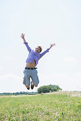 Mid adult man jumping in meadow