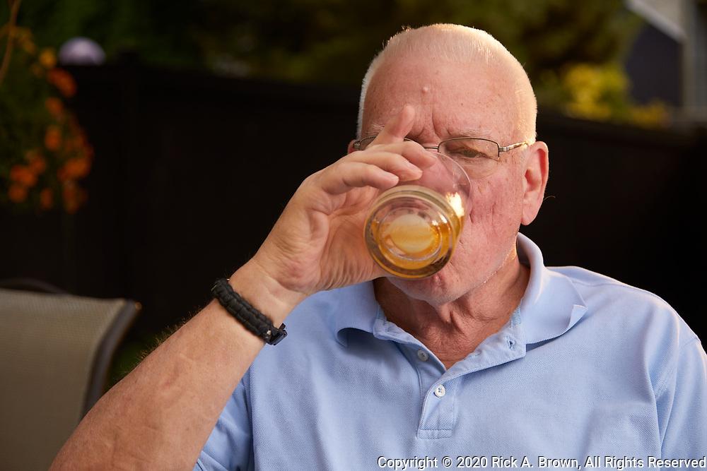 Senior man enjoying rye whiskey on his deck.