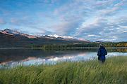 Man watching morning alpenglow on Primrose Ridge above Otto Lake, Healy, Alaska