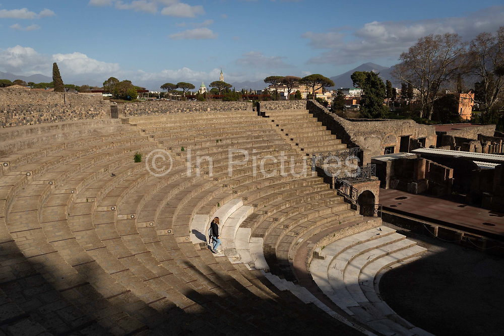A lone woman walks down the steps of the Great Theatre at the Pompeii Archeological Park on Friday 6th March 2020 in Pompei, Italy. Park officials estimate that visitor numbers are down to a sixth of what they would normally be as a result of the spread of Coronavirus, which has prompted the closure of all Italian schools and universities, and the postponing of many sporting events. .