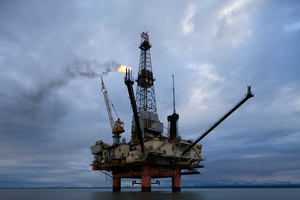USA, Alaska, Natural gas flare from offshore oil drilling rig in Cook Inlet on summer evening