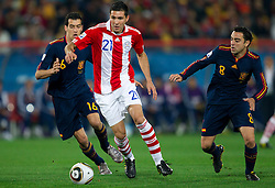 Antolin Alcaraz of Paraguay between Sergio Busquets of Spain and Xavi of Spain during the  2010 FIFA World Cup South Africa Quarter Finals football match between Paraguay and Spain on July 03, 2010 at Ellis Park Stadium in Johannesburg. (Photo by Vid Ponikvar / Sportida)