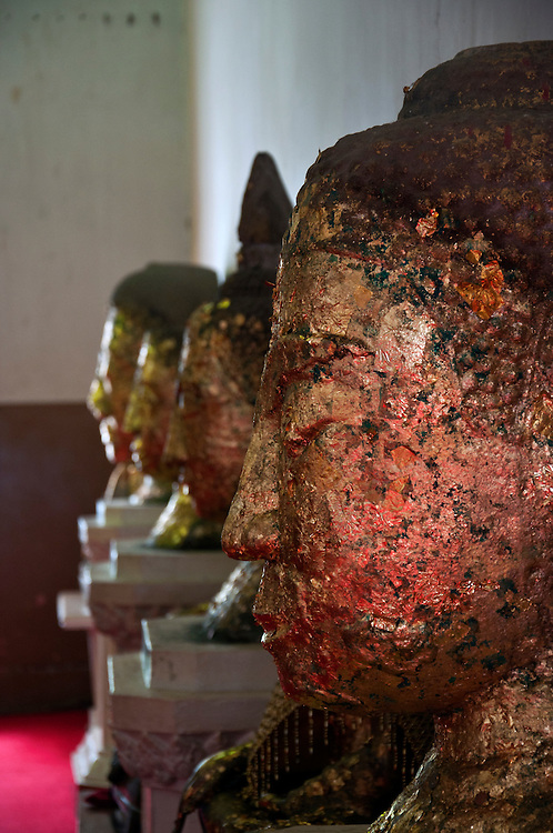 Face sculptures with pieces of gold paper stuck to the outside.