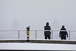 © Licensed to London News Pictures. 24/01/2021. London, UK. Police officers look out over a snowy Greenwich park in South East London. Snow is expected for large parts of the UK and a yellow weather warning is in place in parts of England. Photo credit: George Cracknell Wright/LNP