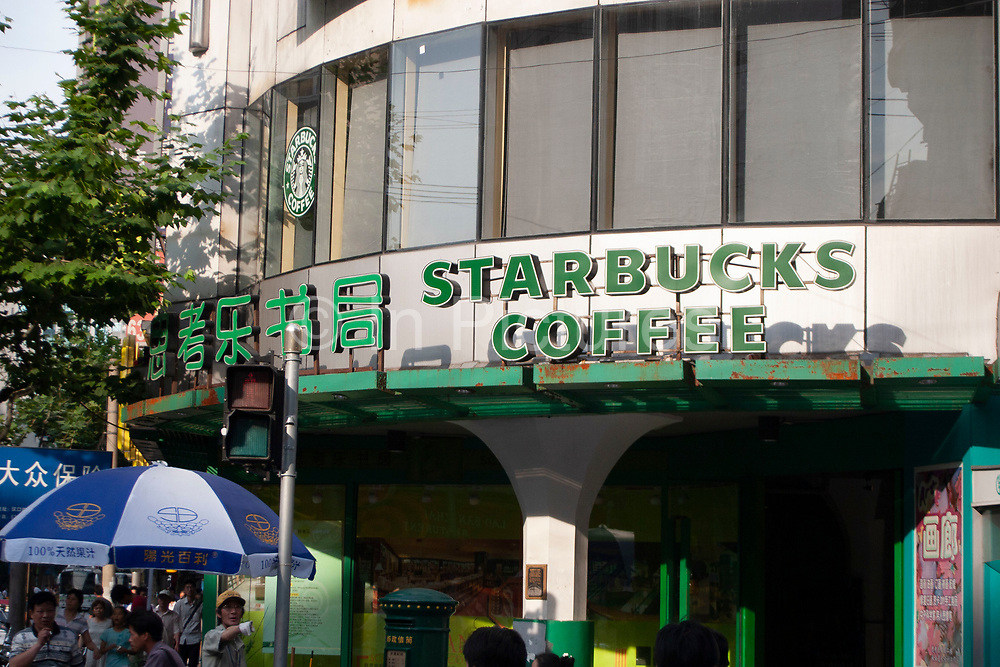 Starbucks Coffee sign in Chinese and English text in Shanghai, China. There are hundreds of fast food stores throughout Shanghai as Chinas hunger for western food increases.