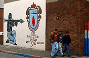 With hands in their pockets and walking in step, three friends pass along a street off the Shankhill Road in Belfast, Northern Ireland, have just passed beneath a Loyalist mural drawn by a paramilitary artist, whose handiwork is based on a well-known representation of a kneeling gunman shouldering a rocket-propelled grenade (RPG) and aiming past the crest of the protestant Ulster Defence Association (UDA), the organisation behind many a sectarian action against neighbouring catholic supporters of the Irish republican Army (IRA). In loyalist areas, the red, white and blue of the British Union Jack is painted on kerbs, houses and railings to signify peoples' allegiance to the crown, having historically followed the 17th century activities of King William of Orange against Catholics.