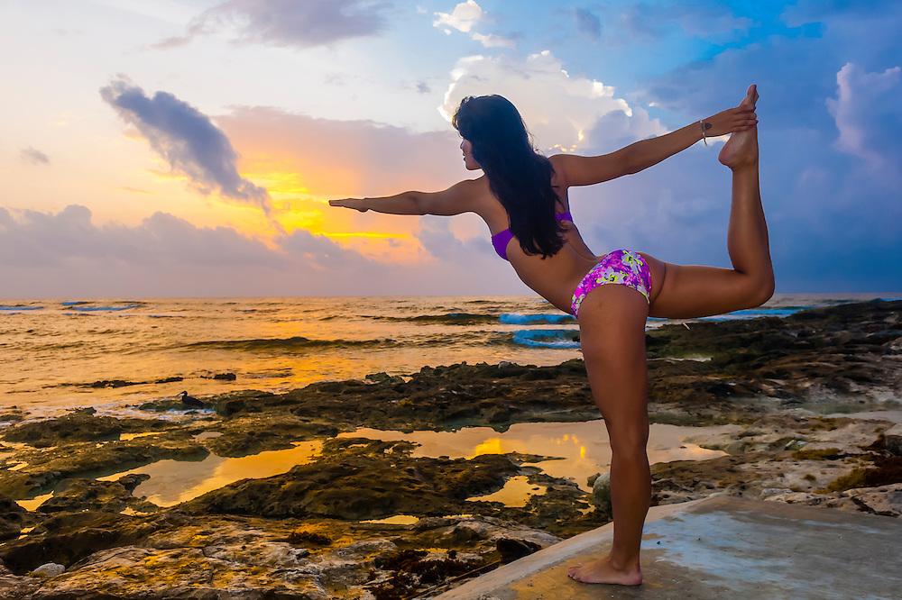 A woman at sunrise doing yoga along the Caribbean Sea at Akumal, Riviera Maya, Mexico.