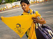 02 DECEMBER 2014 - BANGKOK, THAILAND: A man sells yellow scarves with a likeness of Bhumibol Adulyadej, the King of Thailand, before the Trooping of the Colors parade on Sanam Luang in Bangkok. The Thai Royal Guards parade, also known as Trooping of the Colors, occurs every December 2 in celebration of the birthday of Bhumibol Adulyadej, the King of Thailand. The Royal Guards of the Royal Thai Armed Forces perform a military parade and pledge loyalty to the monarch. Historically, the venue has been the Royal Plaza in front of the Dusit Palace and the Ananta Samakhom Throne Hall. This year it was held on Sanam Luang in front of the Grand Palace. Yellow is widely regarded to be the color of the King and people wear yellow to honor the monarch.     PHOTO BY JACK KURTZ