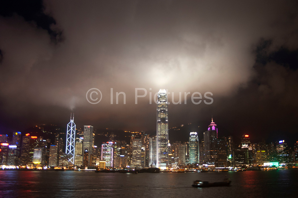 Clouds form over the peak at sunset and collect over the Hong Kong dramatic night skyline. Many of Hong Kong's distinctive buildings line up including the once dominant Bank of China building. Two International Finance Centre now towers over the skyline at 88 stories 415m tall, lighting up the clouds it nearly reaches. Below in the water a Star Ferry crosses from the main terminal at Tsim Sha Sui in Kowloon to Central.