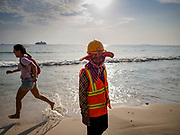 """12 FEBRUARY 2019 - SIHANOUKVILLE, CAMBODIA: A Cambodian construction worker walks past a Chinese tourist running down the beach near the Blue Bay resort development. Blue Bay is a Chinese casino and resort being built in Sihanoukville. There are about 50 Chinese casinos and resort hotels either open or under construction in Sihanoukville. The casinos are changing the city, once a sleepy port on Southeast Asia's """"backpacker trail"""" into a booming city. The change is coming with a cost though. Many Cambodian residents of Sihanoukville  have lost their homes to make way for the casinos and the jobs are going to Chinese workers, brought in to build casinos and work in the casinos.       PHOTO BY JACK KURTZ"""