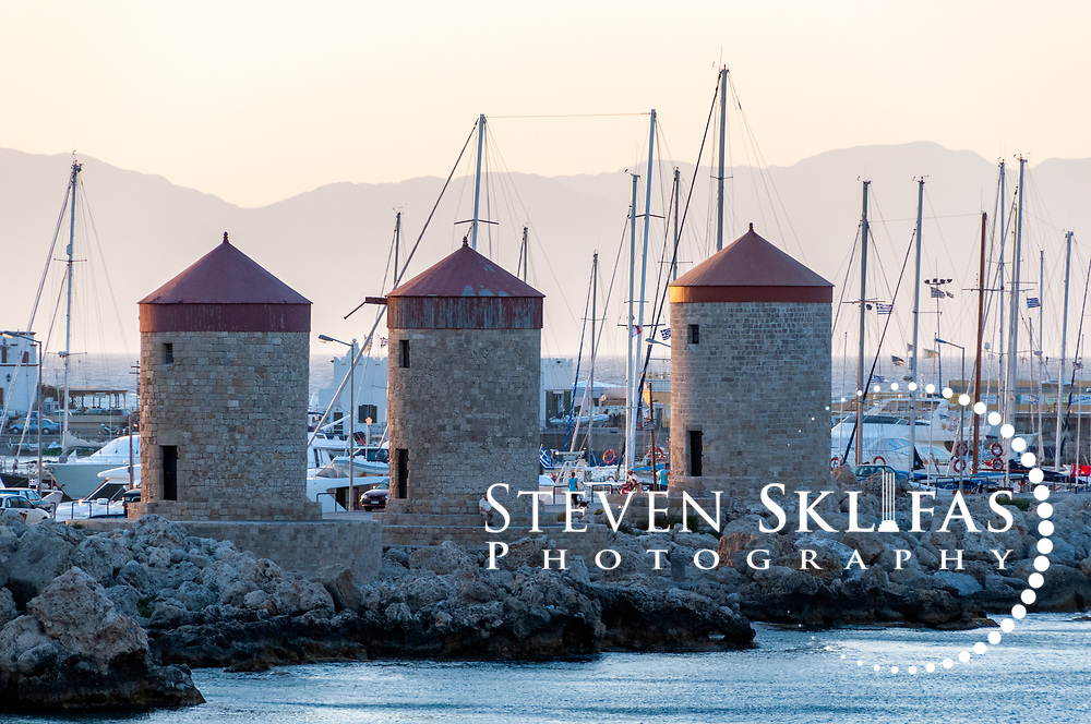 Rhodes. Greece. Three medieval windmills located on the promontory which overlooks Mandraki harbour in Rhodes town. Rhodes town is on the island of Rhodes which is the largest of the Dodecanese Island group and one of the most popular Greek Islands.