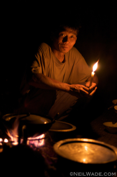 The porter and cook for a three day trek in the mountains surrounding Kalaw, Burma (Myanmar) prepares supper by candlelight.
