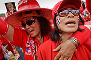 """Mar. 26, 2009 -- BANGKOK, THAILAND: Women at an anti-government protest in Bangkok, Thailand. More than 30,000 members of the United Front of Democracy Against Dictatorship (UDD), also known as the """"Red Shirts""""  and their supporters descended on central Bangkok Thursday to protest against and demand the resignation of current Thai Prime Minister Abhisit Vejjajiva and his government. Abhisit was not at Government House Thursday. The protest is a continuation of protests the Red Shirts have been holding across Thailand in March.  Photo by Jack Kurtz"""