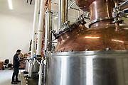 Vishal Gauri works on the still at 10th Street Distillery in San Jose, California, on September 4, 2019. (Stan Olszewski for Content Magazine)