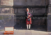 Stock photo of a blond Scottish bagpiper with tartan kilt and white knee-high socks blowing his bagpipe.  He is standing close to the main entrance of St. Giles Cathedral.  His attache case is open for collecting money.  His bagpipe is covered with the tartan of the same pattern.<br /> Photo of Edinburgh, Scotland by Tomoko Yamamoto