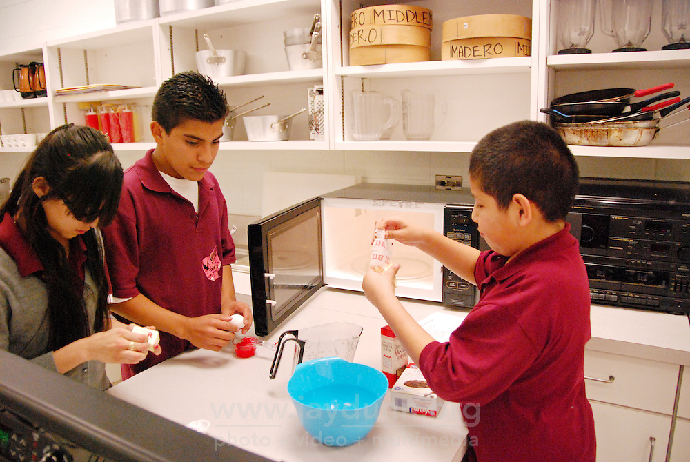 """USA, Chicago, IL, January 26, 2010. Yasmin Acuna, Brandon Oliveros, and Marlon Maya hard at work. Concentrating on four crucial areas, """"Education, Violence Prevention, Cultural Enrichment, and Economic Development,"""" ENLACE Chicago tries to make a positive difference to the residents of the predominantly Latino neighborhood of Little Village. Partnered with Francisco Madero Middle School, for example, ENLACE runs a comprehensive program that successfully integrates the day school with """"after-school,"""" offering academic help with homework, strategies for reading, and a full schedule until 6:00 PM of enrichment programs like culinary arts, music and audio production, and contemporary dancing. Through this kind of direct outreach to more than 5,000 participants in schools and clubs, ENLACE creates opportunities and improves development in this underserved Chicago community. Photo for Hoy by Jay Dunn."""