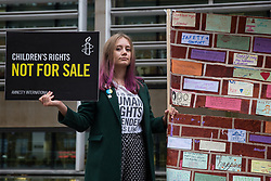 London, UK. 25 November, 2019. A campaigner from Amnesty International UK's Children's Human Rights Network protests outside the Home Office to call on the British Government to stop selling children's rights. Currently, the Home Office charges £1,012 for citizenship applications, including for children living in poverty or local authority care, whilst the cost of processing an application is £372. Thousands of children with rights to British citizenship are prevented from claiming their rights due to excessive fees.